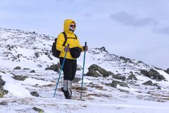 Aged woman is engaged in trekking in winter highlands. Aged hiker woman in bright sportswear is engaged in trekking in winter highlands Stock Images