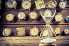 Aged hourglass on the background of clocks Royalty Free Stock Image