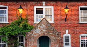 Aged house facade with two burning lantern. Aged house facade, brickwall with two burning lantern Royalty Free Stock Photos