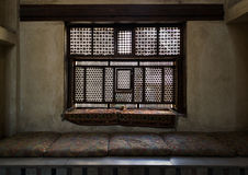 Aged interleaved wooden window and a built-in couch Stock Photos