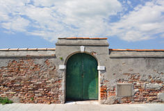 Aged Italian brick wall with arched doorway. Very old brick and plaster wall with arched doorway in an Italian village royalty free stock photos