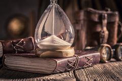 Aged journal and hourglass as a concept of journey memories. On old table royalty free stock photo