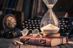 Aged journal and hourglass with binocular, compass and books. On old table stock image