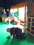 A aged ladhaki woman paying at the Shey Palace temple Royalty Free Stock Photo