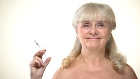 Aged lady holding syringe with insulin, diabetes prevention, timely diagnostics. Stock photo royalty free stock images