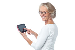 Aged lady operating touch pad device. Senior citizen working on new tablet pc Stock Photography
