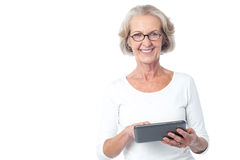 Aged lady operating touch pad device. Senior citizen working on new tablet pc Royalty Free Stock Photos