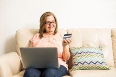 Aged lady shopping online with her credit card. Mature granny buying stuff online with her credit card an her computer on her legs sitting on the couch at home Royalty Free Stock Photography