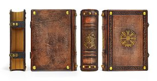 Aged leather book with gilded ancient viking symbols the Vegvisir on the front cover plate and the Cernunnos on the spine royalty free stock photos