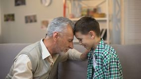 Aged male and boy touching foreheads, friendship between grandpa and grandson