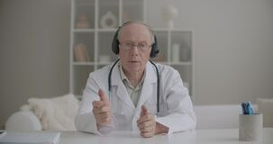 Aged male doctor dressed white gown, glasses and headphones is communicating online, frontal medium portrait