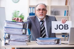 Aged male employee unhappy with excessive work. The aged male employee unhappy with excessive work stock image