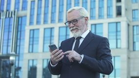 Aged male in formalwear scrolling phone standing near office center reading news. Stock footage stock video footage