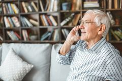 Senior man at home retirement concept sitting phone call. Aged male at home in the living room sitting on the coach answering phone smiling royalty free stock photos