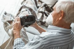 Senior man at home retirement concept sitting holding virtual reality headset close-up. Aged male at home in the living room sitting on the coach holding virtual royalty free stock images