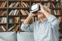 Senior man at home retirement concept sitting looking into virtual reality headset. Aged male at home in the living room sitting on the coach looking into stock image