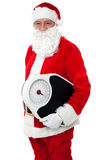 Aged male Santa holding weighing scale Stock Photo