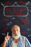 Aged man advertising sale using chalk inscriptions on blackboard Stock Images