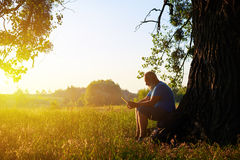 Aged man beneath a tree on the background of sunset in the field. Aged man is sitting beneath a tree with his data tablet and enjoying the moment of relaxation Royalty Free Stock Images