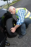 Aged man changing leaking tire on verge. Aged man changing leaking tire on the verge Stock Photo