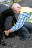 Aged man changing leaking tire on verge. Aged man changing leaking tire on the verge Stock Images