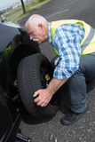 Aged man changing leaking tire on verge. Aged man changing leaking tire on the verge Stock Photography