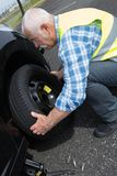 Aged man changing leaking tire on verge. Aged man changing leaking tire on the verge Royalty Free Stock Photos