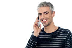 Aged man communicating with friend. Smart middle aged man talking on mobile phone Stock Images