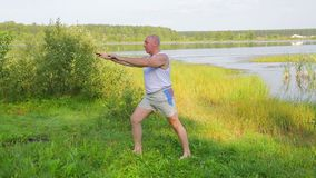 Aged man doing stretching exercises on the lake in the morning. Overall plan stock video