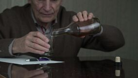 Aged man drinks whiskey from transparent glass sitting