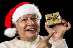 Aged Man With Emphatic Look And Golden Gift. Smiling old man with challenging gaze is gesturing with his raised right index finger. He is pointing at his left Stock Photos