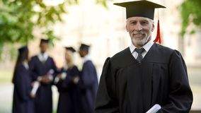 Aged man in graduation outfit, professor obtaining new degree, academic career. Aged men in graduation outfit, professor obtaining new degree, academic career royalty free stock photos