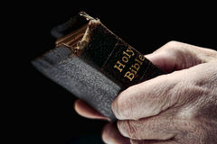 Aged Man Hands Holding Old Antique Holy Bible Book. Aged man hands firmly holding and clinching an old and damaged antique Holy Bible Christian religious book stock photos