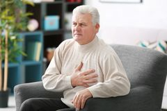 Aged man having heart pain. At home stock photography