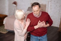 Aged man with heartache near wife. Im not good. Portrait of elderly men standing and touching his heart area while his loving wife supporting him during this Royalty Free Stock Photography