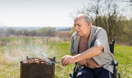 Aged Man on his Wheelchair Grilling Under the Sun Stock Image