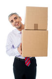 Aged man holding cardboard boxes. Manager handing pile of cardboard boxes Stock Photos