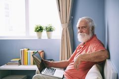 Aged man with laptop royalty free stock images