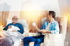 Aged man looking at his handsome son while drinking coffee with him Stock Images
