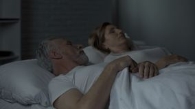 Aged man lying in bed awake, looking at woman sleeping beside him, annoyance