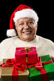 Aged Man Offering Three Wrapped Christmas Presents. Kind male pensioner with Father Christmas hat and white sweater. Gentle smile, attentive gaze. He is offering Royalty Free Stock Image