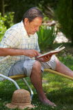 Aged man reading book. Healthy looking aged man is his late 70s sitting in garden at home and reading book Stock Photography
