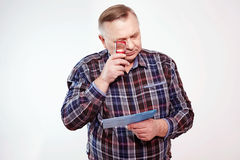 Aged man reading with magnifier Stock Photography