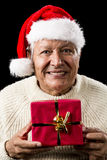 Aged Man With Santa Claus Cap and Red Xmas Gift. Friendly male pensioner with red Father Christmas hat and white pullover. Coy smile. His hands are holding a Royalty Free Stock Images