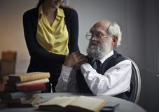 A girl holding aged man`s hands stock photography
