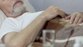 Aged man sleeping on bed with glass standing in front, drugs for insomnia. Stock footage stock video footage