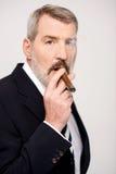 Aged man smoking cigar over white Stock Image