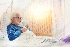 Aged man staying in bed and drinking hot coffee Stock Photos
