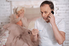 Aged man with thermometer calling emergency Stock Image