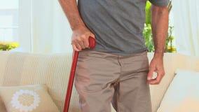 Aged man using a walking stick stock video
